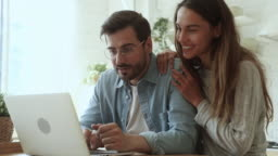Overjoyed young couple using laptop excited by online win