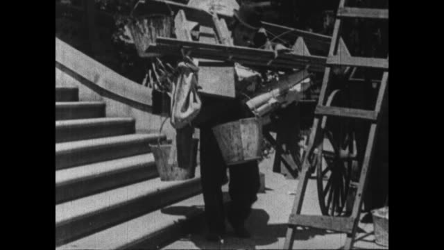 1915 overloaded charlie chaplin struggles to bring decorating supplies into house - pericolo video stock e b–roll