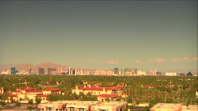 overlooking midrise buildings trees the strip las vegas boulevard w/ hotels casinos in distance mountain range bg sin city gambling vacation... - mid distance stock videos & royalty-free footage