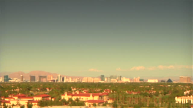 overlooking midrise buildings trees the strip las vegas boulevard w/ hotels casinos in distance mountain range bg out/in focus sin city gambling... - mid distance stock videos & royalty-free footage
