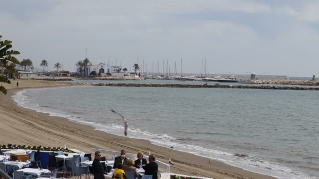 Overlooking the beach of Marbella in Andalusia in Spain in front people are eating in a restaurant in the background the marina can be seen