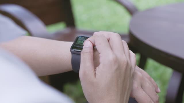vidéos et rushes de overshoulder shot de la personne utilisant la montre intelligente dans l'arrière-cour - montre