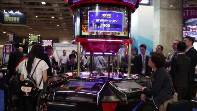 Oversized dice spin inside a glass display at an electronic craps table at the Macao Gaming Show in Macau China on Tuesday Nov 15 Attendees...