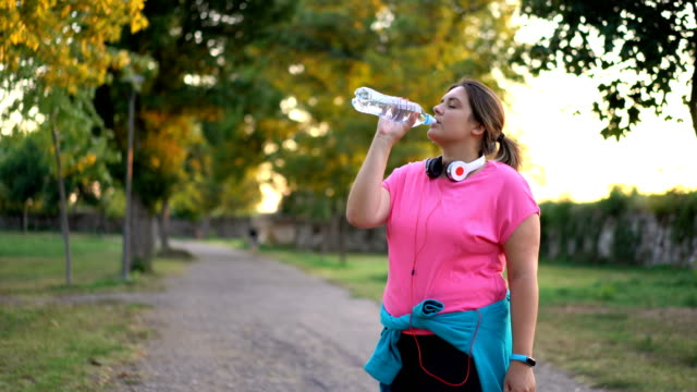 oversized woman drinking water after running - overweight stock videos & royalty-free footage