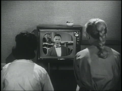 b/w 1956 rear view over-the-shoulder 2 teen girls watch alan freed on television - fernsehserie stock-videos und b-roll-filmmaterial