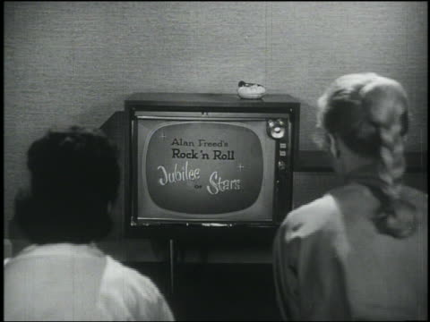 "stockvideo's en b-roll-footage met b/w rear view over-the-shoulder 2 teen girls watch ""alan freed's rock 'n roll jubilee of stars"" on tv / dolly shot to tv - 1956"