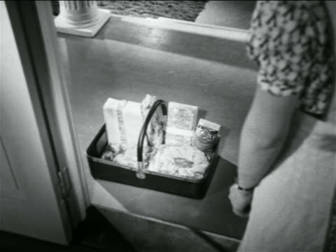 stockvideo's en b-roll-footage met b/w 1938 over-the-shoulder basket of items sitting on front porch / industrial - 1938