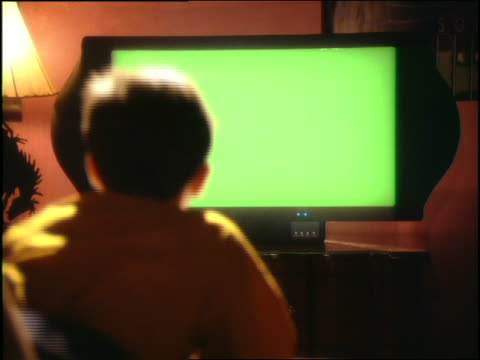 vidéos et rushes de over-the-shoulder boy lying on bed playing video game (blank screen) - écran blanc