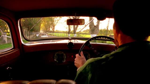 vidéos et rushes de over-the-shoulder car point of view man driving 1935 delahaye 135 coupe on tree lined country road / provence, france - intérieur de véhicule