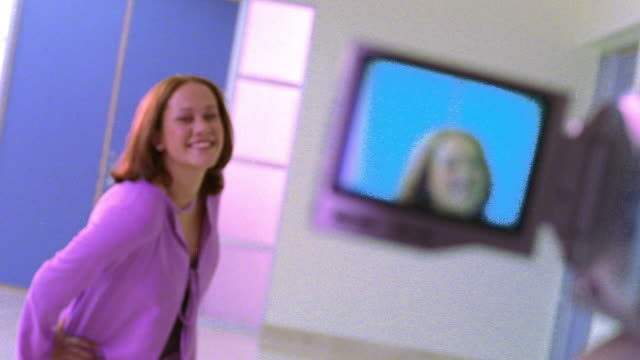 over-the-shoulder close up viewfinder screen of video camera with redheaded woman posing / PAN rack focus to woman