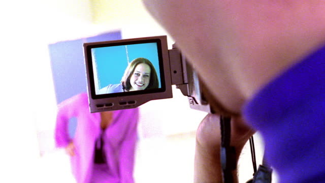 vídeos de stock, filmes e b-roll de overexposed over-the-shoulder close up viewfinder screen of video camera with redheaded woman posing / pan rack focus to woman - superexposto