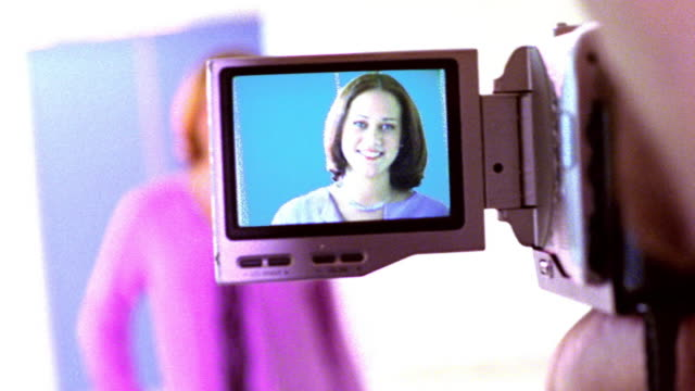OVEREXPOSED over-the-shoulder close up viewfinder screen of video camera with redheaded woman posing / PAN rack focus to woman
