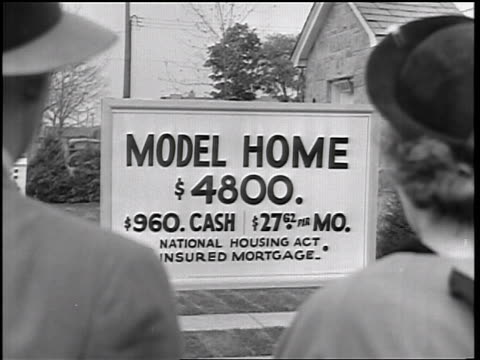 b/w 1935 over-the-shoulder couple looking at sign with prices in front of model home / educational - 1935 stock videos & royalty-free footage