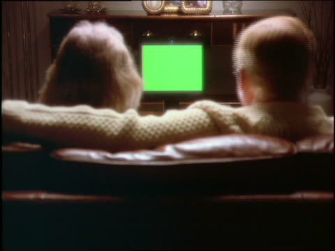 over-the-shoulder couple sitting on sofa looking at television/computer - anno 1997 video stock e b–roll