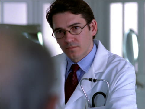over-the-shoulder male doctor wearing eyeglasses listening to patient talking in foreground + nodding