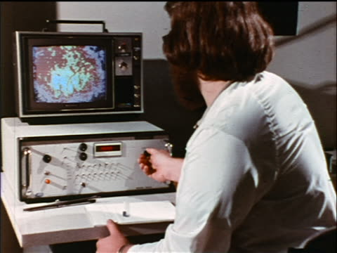 1973 over-the-shoulder man looking at geological survey map on computer screen / industrial - old computer monitor stock videos & royalty-free footage