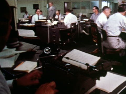 1960 over-the-shoulder man typing on typewriter in newspaper office / men working at desks in background / documentary - journalist video stock e b–roll