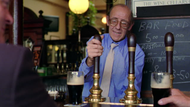 over-the-shoulder of customer talking with bartender who is pouring beer from tap + laughing / dublin, ireland - pub stock videos & royalty-free footage