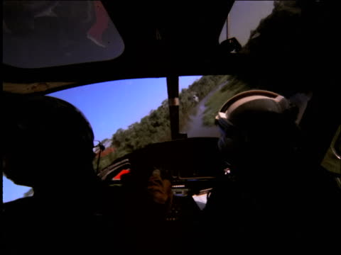 over-the-shoulder point of view of pilots in helicopter cockpit flying / Amazonia, Brazil