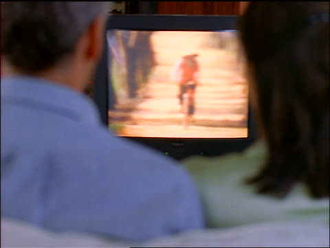 vídeos de stock, filmes e b-roll de rear view over-the-shoulder seated couple watching television (asian farmer + bicycle rider on tv) - 1998