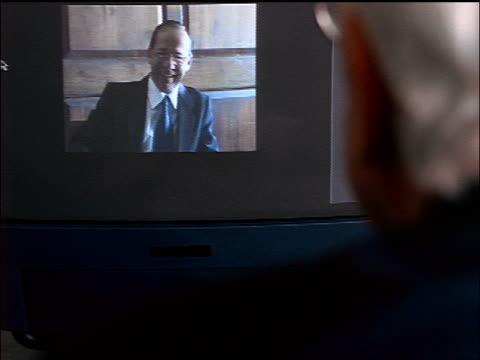 vídeos de stock, filmes e b-roll de rear view over-the-shoulder senior businessman teleconferencing with laughing businessman on computer screen - vestuário de trabalho formal