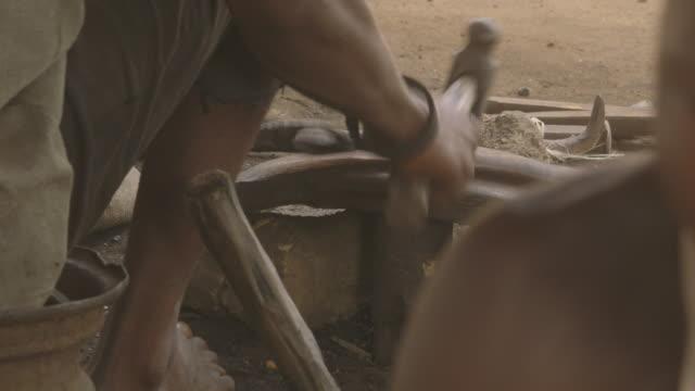 vídeos de stock e filmes b-roll de over-the-shoulder shot of metal being hammered at a workshop in sierra leone. - ferro metal
