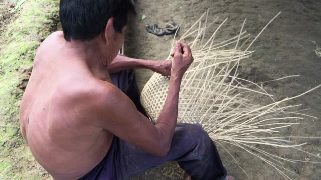 Over-the-shoulder shot of middle-aged Kichwa Indian male weaving a natural plant-based basket in the autonomous indigenous region of Sarayaku in the Ecuadorian Amazon