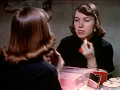 1953 over-the-shoulder teen girl putting on lipstick + combing hair in mirror / educational - di archivio video stock e b–roll