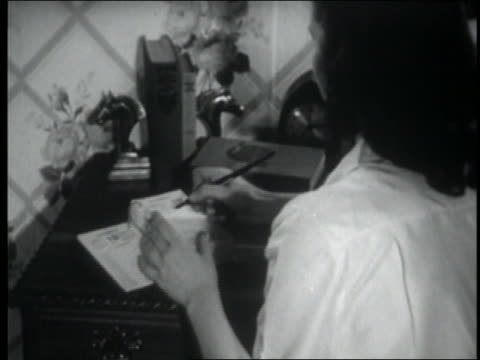 b/w 1947 over-the-shoulder woman sitting + writing in desk calendar - diary stock videos & royalty-free footage