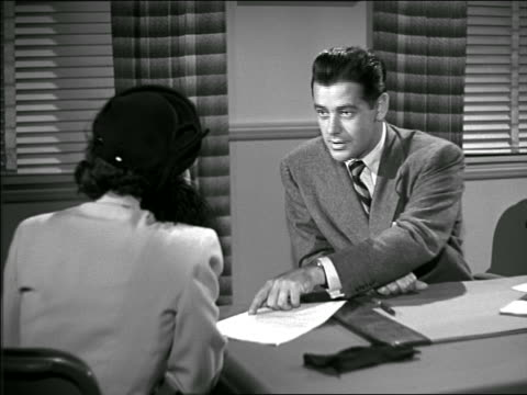 b/w 1949 over-the-shoulder woman wearing hat sitting in office signing contract with businessman - signing stock videos & royalty-free footage