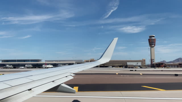over-the-wing point of view of taking off in a commercial airliner jet at phoenix sky harbor international airport in phoenix, arizona on a sunny day - air traffic control tower stock videos & royalty-free footage