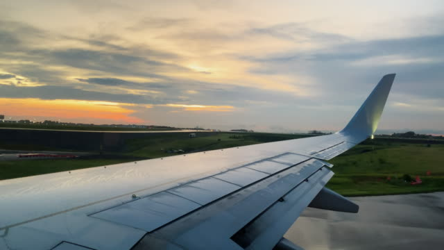 vídeos y material grabado en eventos de stock de over-the-wing point of view of taxing down a runway in a commercial airliner jet at nashville international airport in tennessee at sunset - despegar actividad