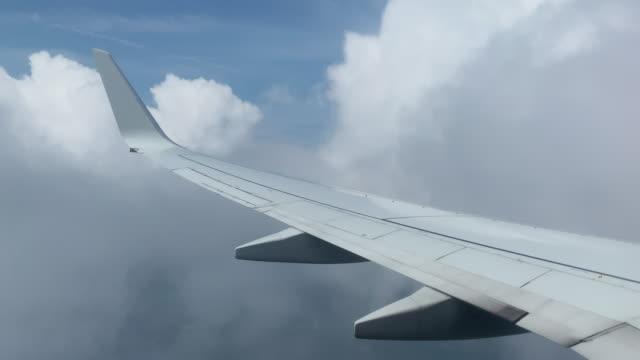 vista over-the-wing da un jet della compagnia aerea commerciale che vola sopra le nuvole e atterra in una giornata di sole - ala di aeroplano video stock e b–roll