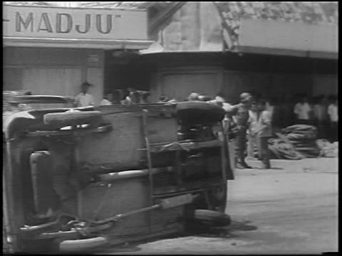 b/w 1967 overturned car troops on street in antichinese riot / jakarta indonesia / newsreel - indonesian ethnicity stock videos & royalty-free footage