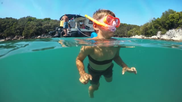 pov over-under: little boy swimming with a dive mask - snorkelling stock videos & royalty-free footage