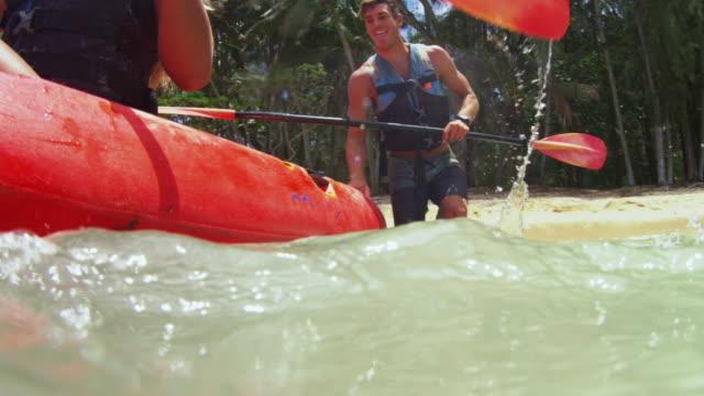 vídeos de stock, filmes e b-roll de over/under shot of a person jumping into a two person kayak - esporte aquático