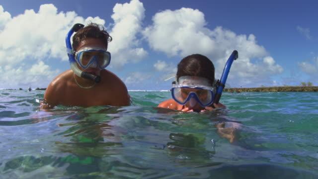 over-under shot of couple diving underwater to snorkle - タートル湾点の映像素材/bロール
