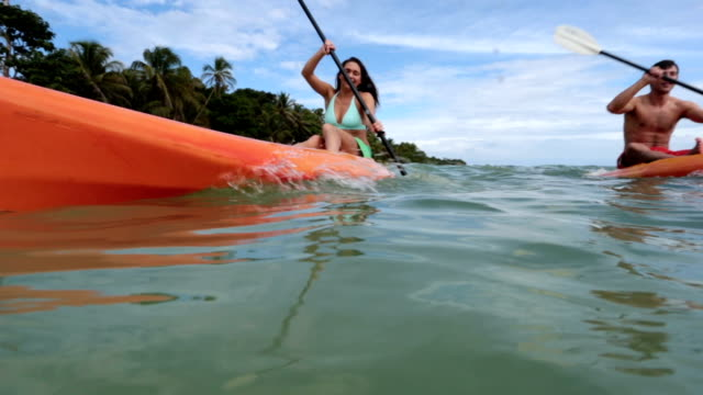 over/under pov shot of man and woman kayaking in ocean along tropical beach. - bikinioberteil stock-videos und b-roll-filmmaterial