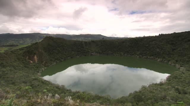 vídeos de stock e filmes b-roll de overview from ridge of laguna de guatavita with cloudy sky and mountain range in b/g, cundinamarca region, colombia - colômbia