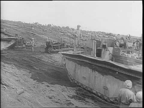 overview front of battleship / wounded gunner and dead sailor on ship / aerial dozens of ships in pacific ocean at shore of iwo jima / japanese... - 海軍点の映像素材/bロール