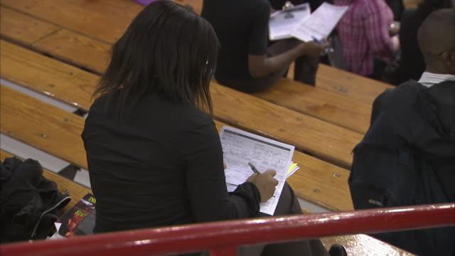 vídeos de stock e filmes b-roll de overview of job fair ms people filling out resumes ms people networking - feira de emprego