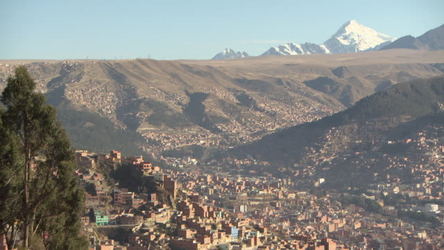 overview of la paz [nuestra seã±ora de la paz/chuquiago marka/chuqiyapu] with mountains and glacier in b/g, bolivia - ボリビア点の映像素材/bロール