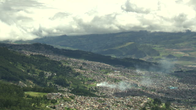 Overview of residential area of Bogotá, Colombia with rising smoke, valley and green hills on a cloudy day.