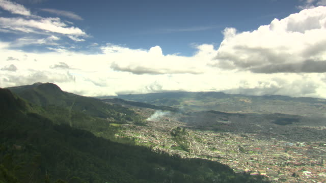 Overview of residential area of Bogotá, Colombia with rising smoke, valley and green hills with blue sky and white clouds