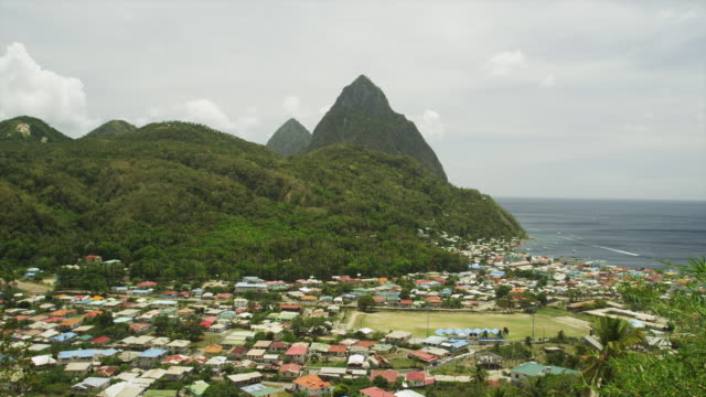 ws ha pan overview of village with mountain peak / soufriere, st. lucius, caribbean - st. lucia stock videos & royalty-free footage