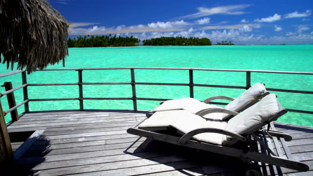 overwater bungalows in tropical aquamarine lagoon bora bora - outdoor chair stock videos and b-roll footage