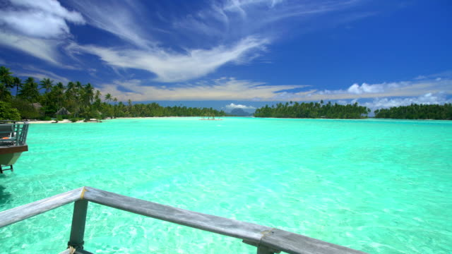 overwater bungalows in tropical aquamarine lagoon bora bora - polynesian ethnicity stock videos & royalty-free footage