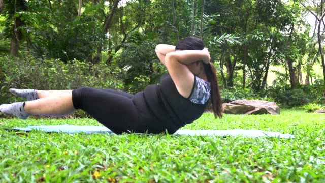 Overweight asian woman practicing exercise at park