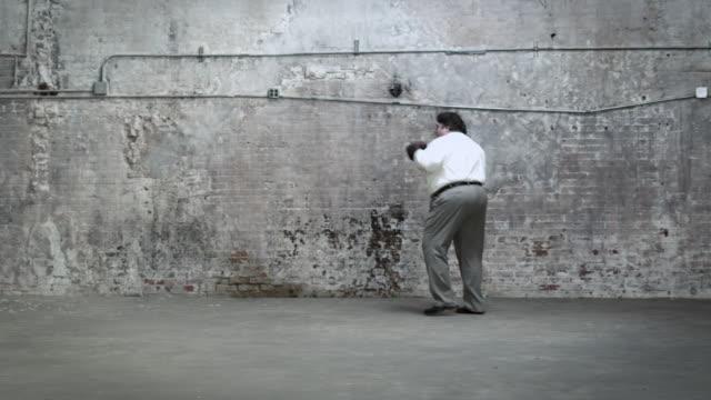 overweight businessman practicing boxing - 中年の男性だけ点の映像素材/bロール