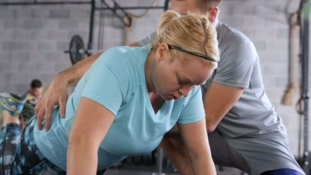 overweight caucasian woman doing knee push ups under the supervision of her male trainer - overweight active stock videos & royalty-free footage